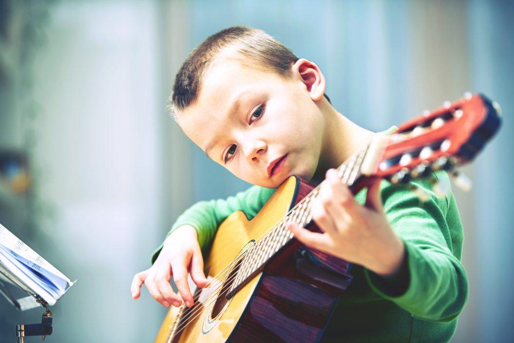 niño pequeño tocando la guitarra
