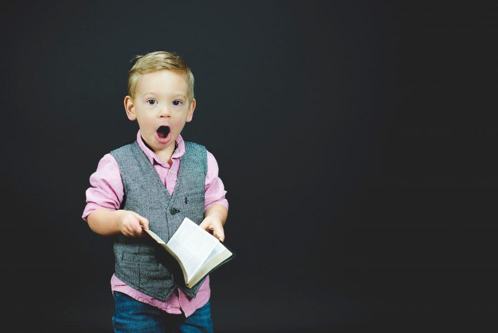 niño con cara de sorprendido leyendo un libro