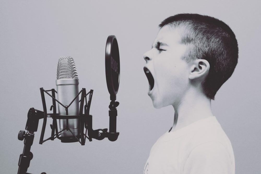 niño cantando con un micrófono