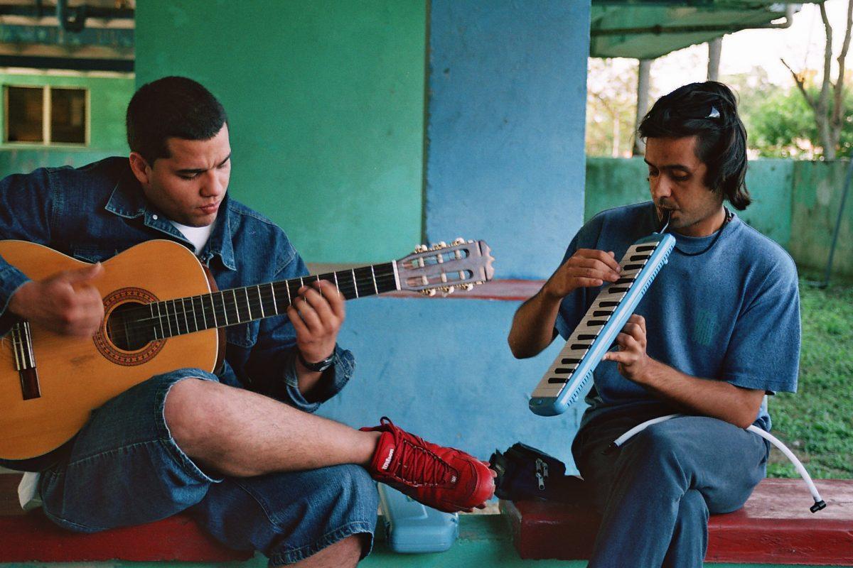 Musicos tocando guitarra y melódica en Cuba